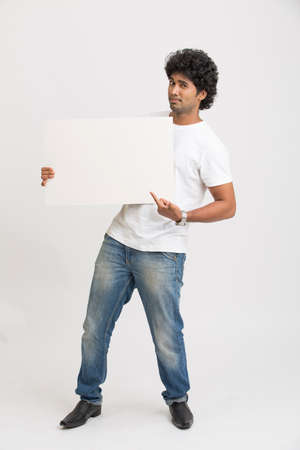 indian girl: Happy smiling young Indian man holding a blank billboard on white background