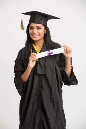 graduate hat: Smiling Indian girl college graduate posing with wearing cap and gown holding diploma on white background.