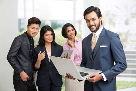 Proud smiling businessman working in laptop with his team business people on white.