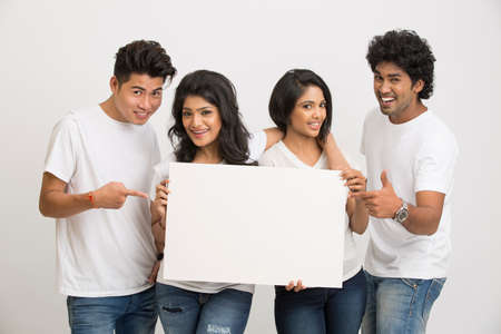 banner ads: Group of Indian young people holding blank white board on white background. Stock Photo