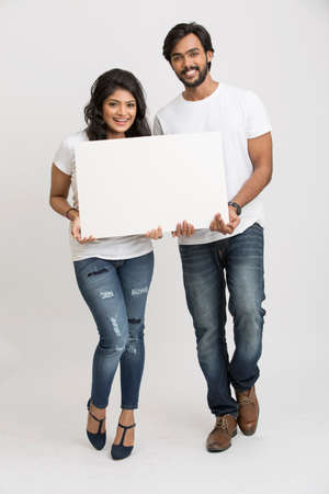 billboard background: Two young Indian people holding a blank billboard white background