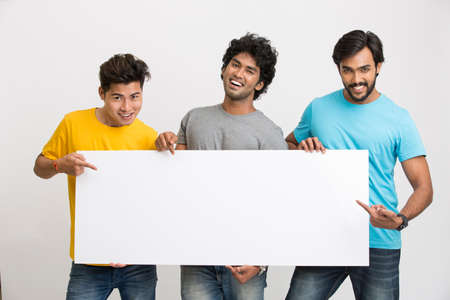 indian teenager: Happy joyful group of friends displaying white boad for your text on white background
