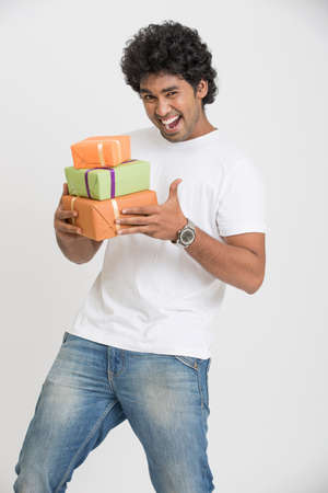 indian sweet: Surprised smart Indian young man with gift boxes on white background