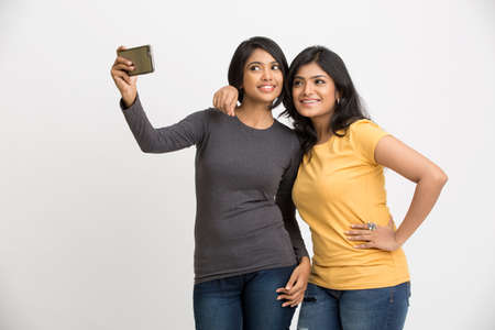brunette girl: Two pretty young women taking selfie with mobile phone