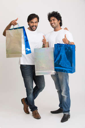 shoppingbags: Cheerful happy two smart young boys with shopping bags on white background.