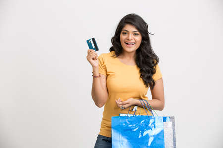 woman credit card: Cheerful smiling Indian young woman with shopping bags and credit card