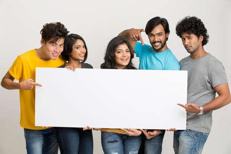 fille indienne: groupe joyeux heureux d'amis affichant boad blanc pour votre texte sur fond blanc
