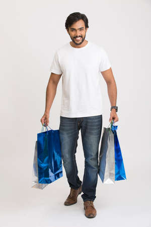 shoppingbags: Cheerful beard smart young man walking with shopping bags on white.