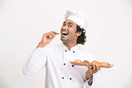 hombre comiendo: Un cocinero de sexo masculino con las galletas en el fondo blanco.