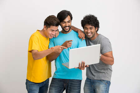 room mate: Smiling cheerful male friends with laptop computer on white background. Stock Photo