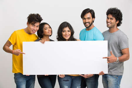 latin students: Happy joyful group of friends displaying white boad for your text on white background