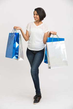carrying girl: Happy Indian young woman showing shopping bags and credit card