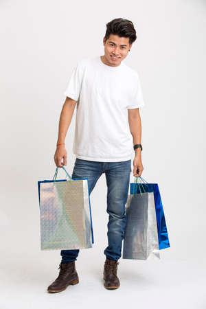 shoppingbags: Happy smart young man standing with shopping bags Stock Photo