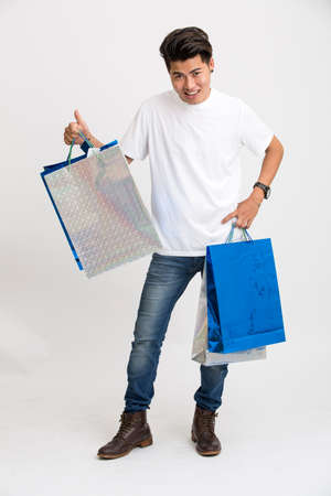 shoppingbags: Cheerful smart young man showing thumbs up with shopping bags.