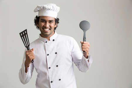 asian cook: Cheerful happy chef holding kitchen utensil isolated on grey background