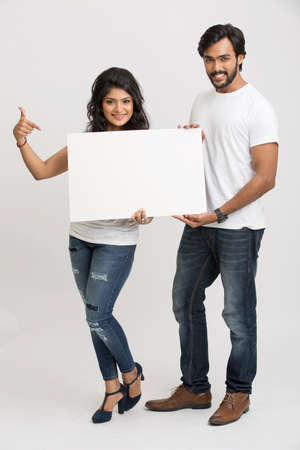 smile girl: Two cheerful young Indian people holding a blank billboard white background