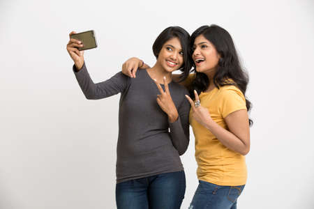 woman pose: Two pretty young women taking selfie with mobile phone