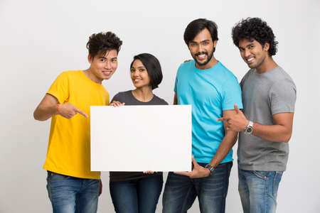 an adult person: Happy joyful group of friends displaying white boad for your text on white background
