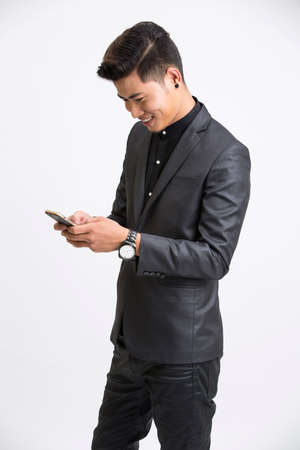 asian guy: Cheerful businessman using mobile phone on white background.