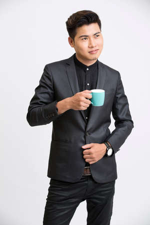 asian guy: Young businessman with coffee cup on white background.
