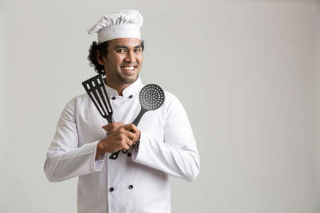 successful man: Cheerful happy chef holding kitchen utensil isolated on grey background