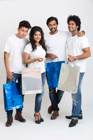 four people: Small happy group of friends standing with shopping bags on white.