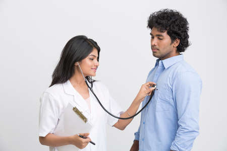 young doctors: Young doctor is examining the patient with a stethoscope.