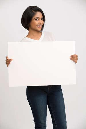 letreros: Feliz sonriente mujer joven con un fondo blanco cartelera en blanco