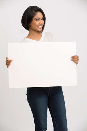 a placard: Happy smiling young woman holding a blank billboard white background