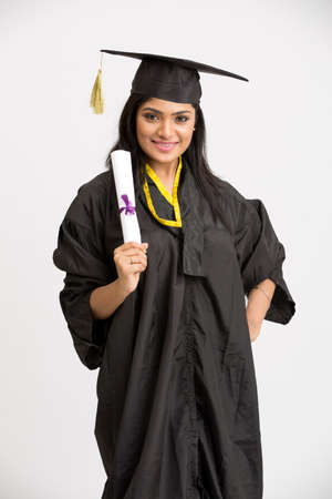 tamilnadu: Indian girl college graduate posing with wearing cap and gown holding diploma on white background.