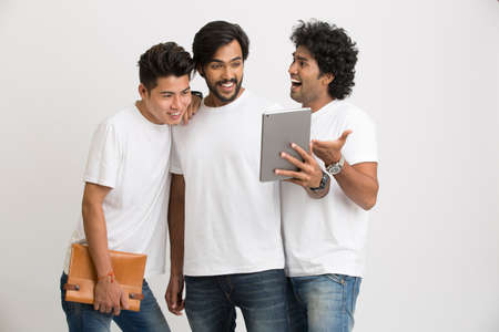 pakistani ethnicity: Successful group of Indian university friends using Pc tablet on white.