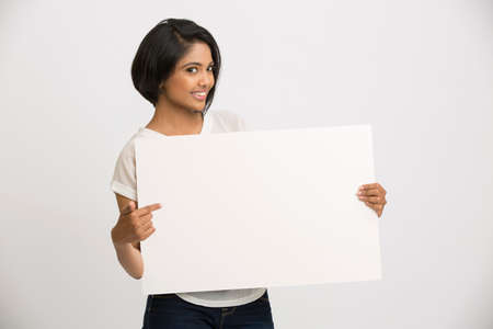 billboard advertising: Beautiful happy young Indian woman holding a blank billboard white background
