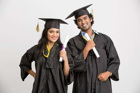 successful student: Cheerful Indian college graduates wearing cap and gown holding diploma on white background