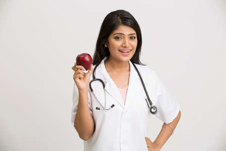 a lady doctor: Smiling Indian female doctor holding red apple on white background.