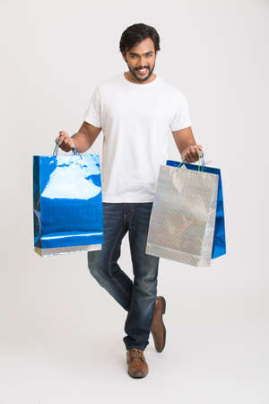 shoppingbags: Happy smart young man posing with shopping bags on white background. Stock Photo