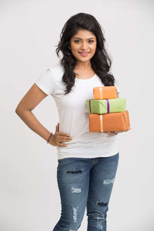 Beautiful Indian young woman with gift boxes on white background