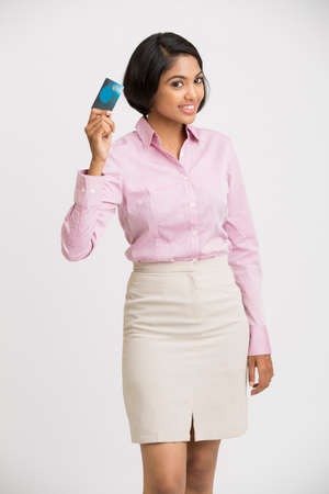 south asian: Young pretty smiling Indian girl showing her credit card to the camera.