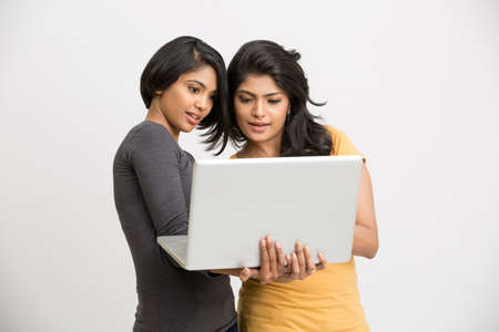 computer education: Happy two young women with laptop on white background.