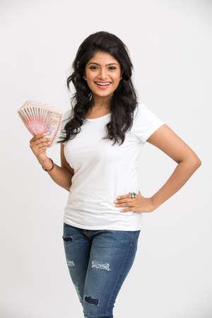 dinero: Chica joven sonriente que lleva a cabo notas rupia en sus manos sobre fondo blanco.