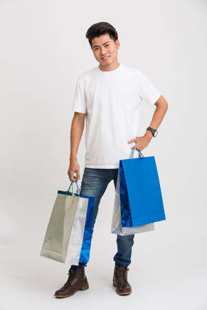shoppingbags: Smart young man posing with shopping bags on white. Stock Photo