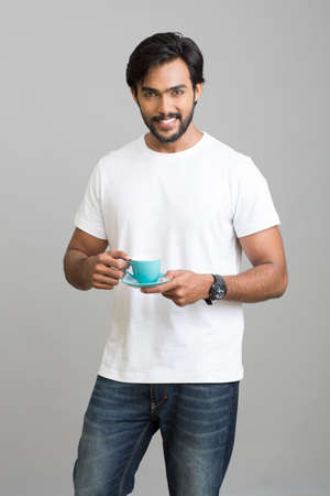 male body: Happy smart young man posing with coffee cup on white background.