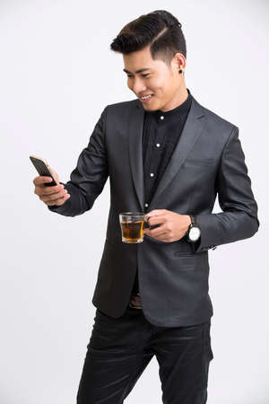 businessman phone: Businessman looking at mobile phone with cup of tea on white background.