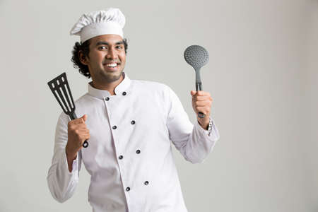 aghast: Cheerful happy chef holding kitchen utensil isolated on grey background