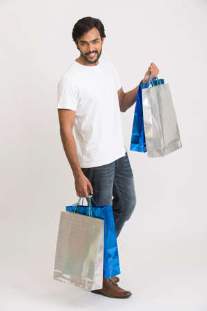 shoppingbags: Cheerful happy smart young man with shopping bags on white background. Stock Photo