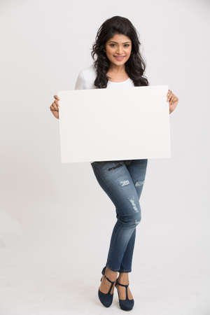 hold: Happy smiling young Indian woman holding a blank billboard white background Stock Photo