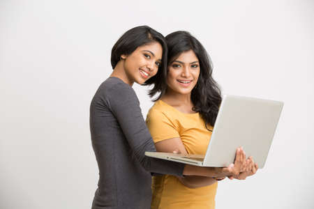 girl with laptop: Two young women with laptop and looking at the camera on white background. Stock Photo
