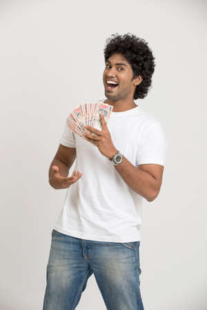 hold on: Happy Indian businessman with rupees on white background.
