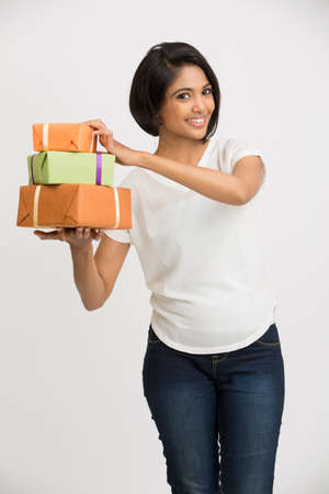cute girl: Happy smiling Indian young woman showing her gift boxes on white background Stock Photo