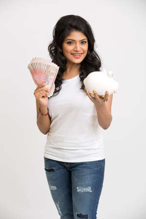 rupee: Smiling young girl holding rupee notes and piggy bank in her hands on white background. Stock Photo