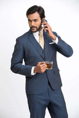 navy blue suit: Businessman looking at mobile phone and holding cup of coffee, isolated on white background.